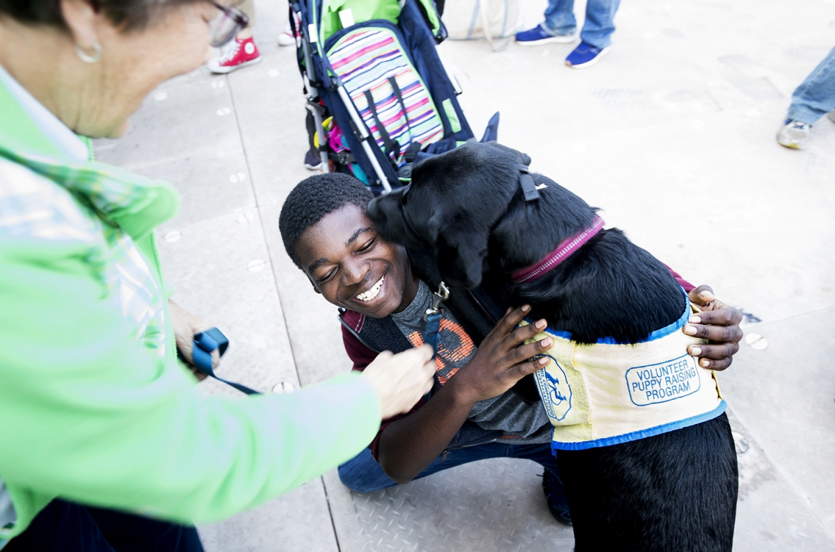"Keon Stewart, 14, and a support dog, on the dog's vest is a lable ""voulunteer puppy raising program"""