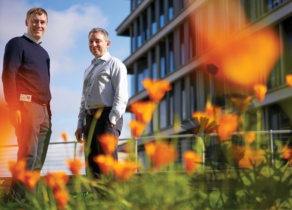 Ophir Klein and Jeffrey Bush stand outside by a bed of flowers