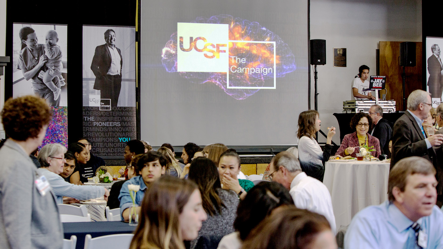 people eat in a room with a screen that says UCSF: The Campaign behind them