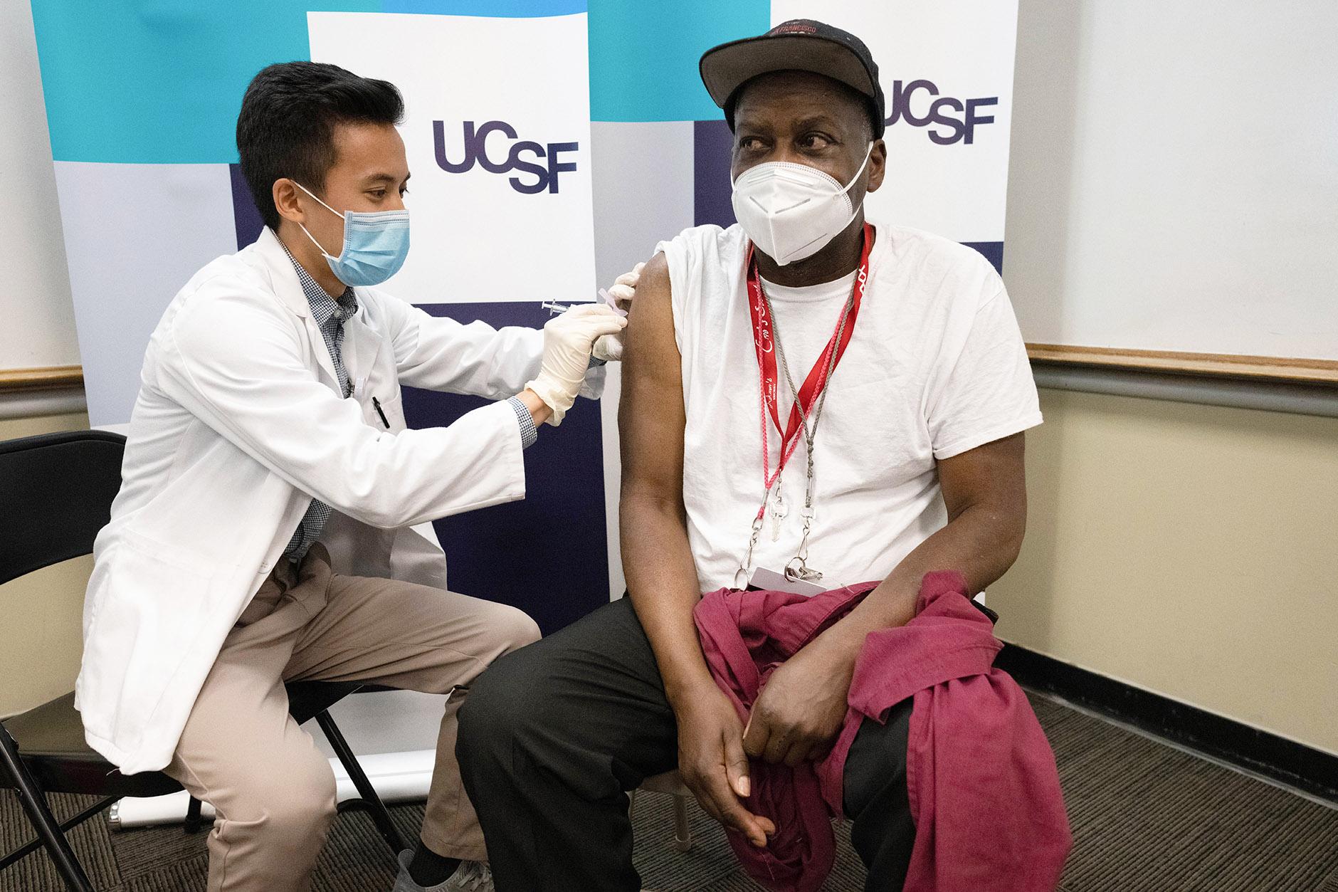 man receives COVID-19 vaccination shot