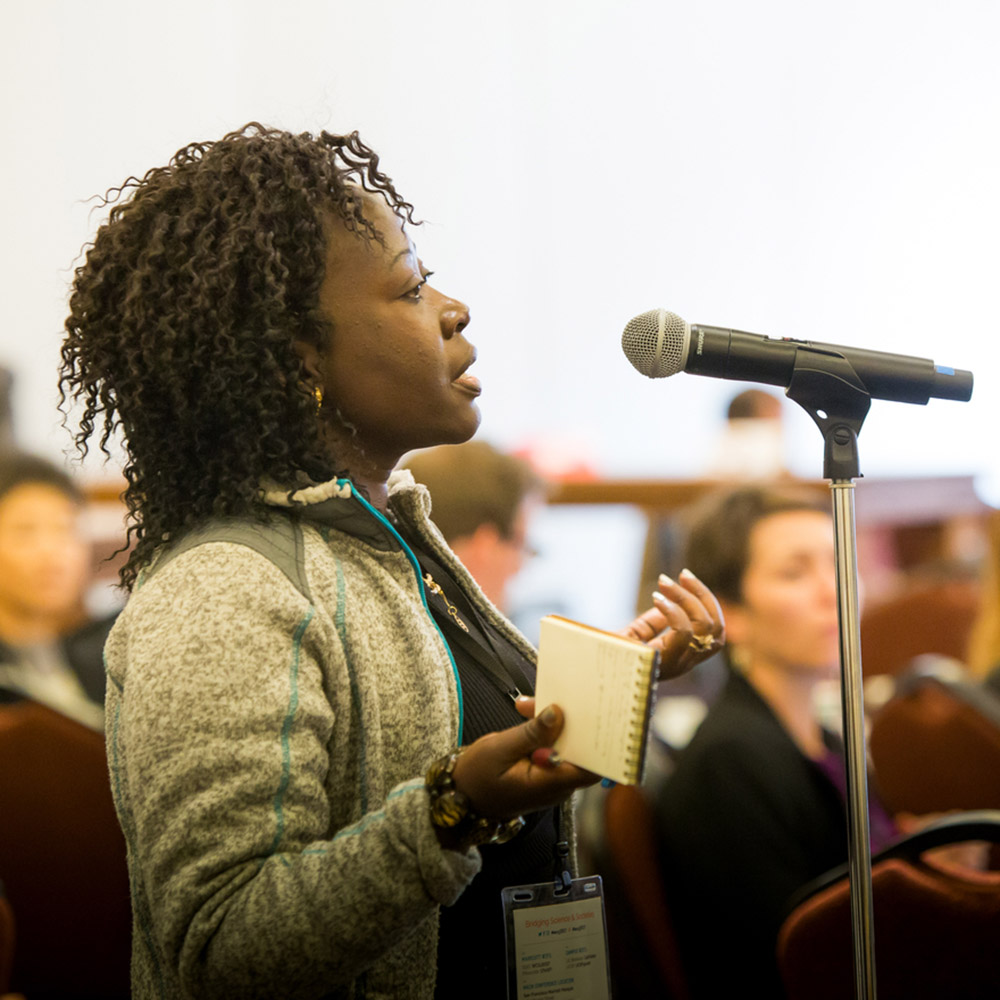 An audience member asks a question of the speakers during the WCSJ Conference