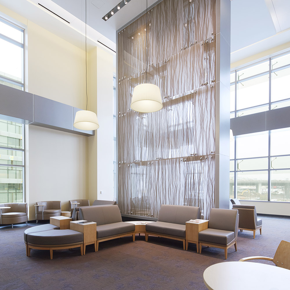 A spacious, sunlit lobby with high ceilings and low lying chairs