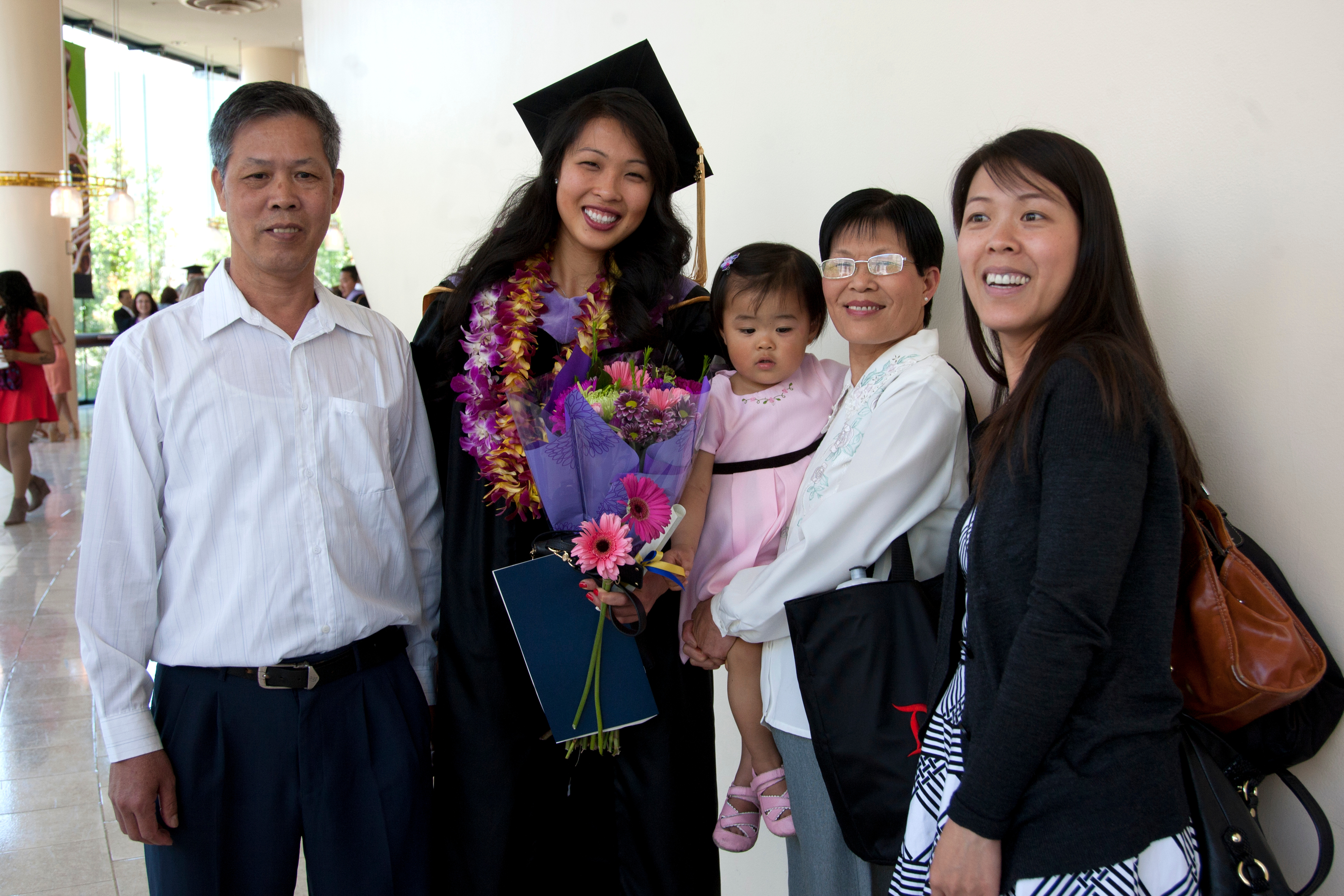 UCSF dental school graduate Cai Zhang takes a family photo after the commencement ceremony.