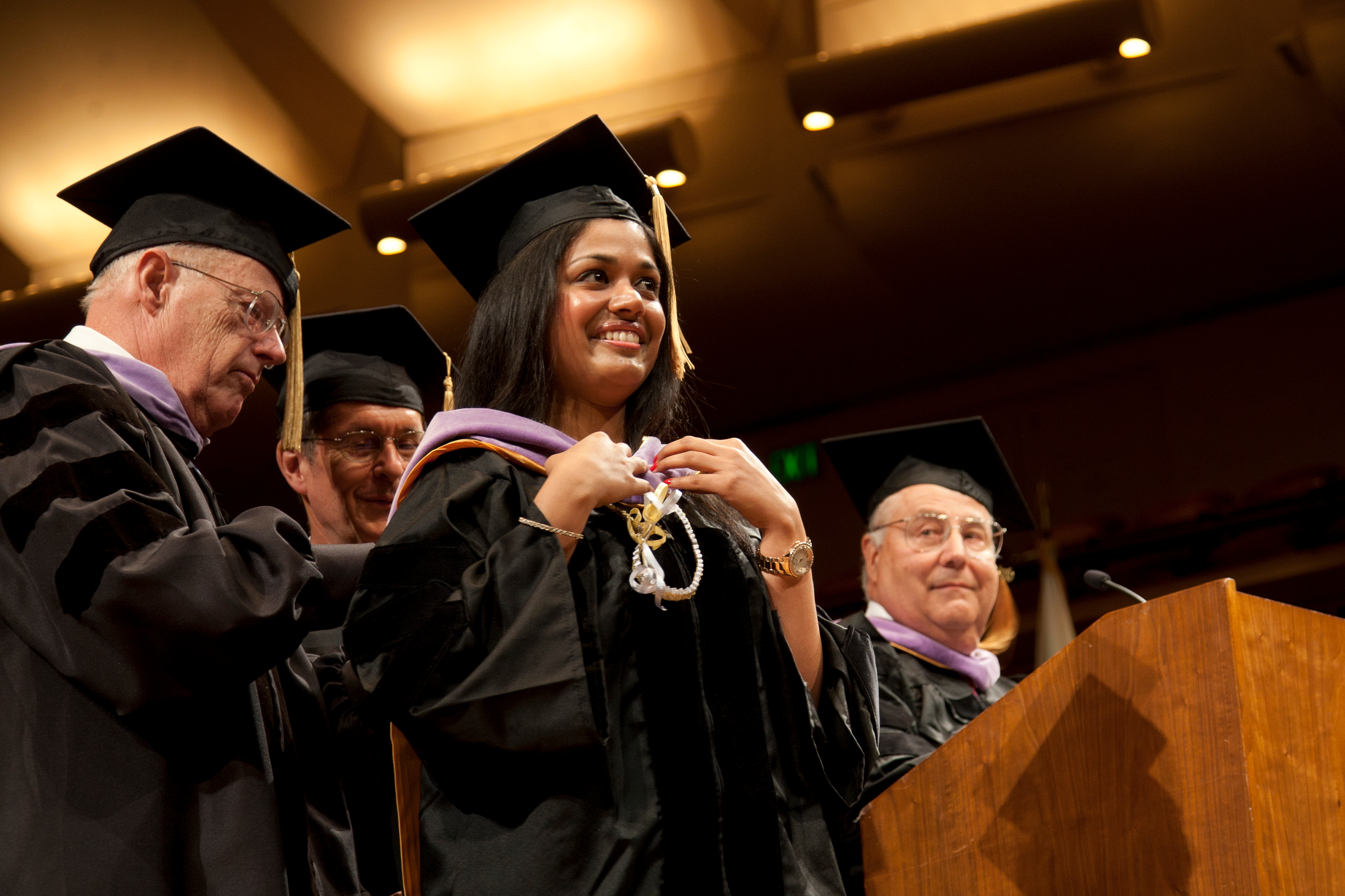 Graduate Prema Aggarwal is hooded during the commencement ceremony. The most important element of academic regalia is the hood, which is lilac, the color that denotes a doctor of dentristry.