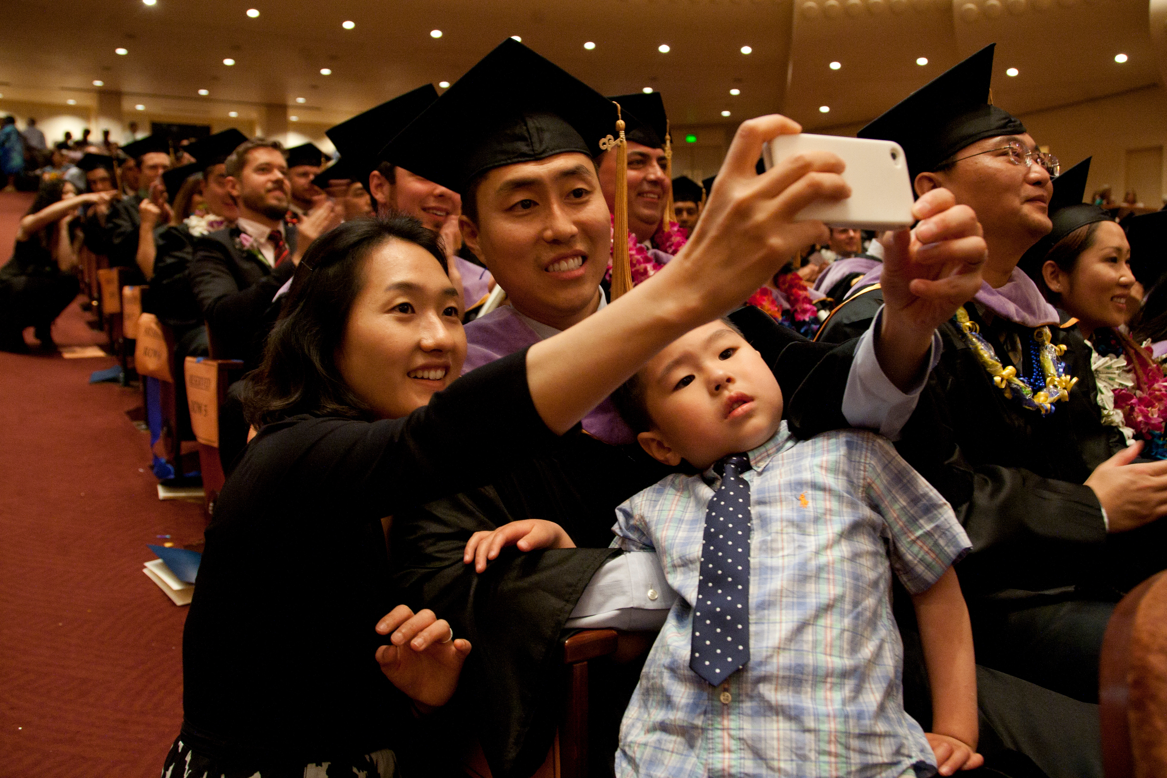 Dental school graduate Kwang Chang takes a family photo with his wife Myung Hee Song and son, Ethan, 4, during the commencement ceremony.