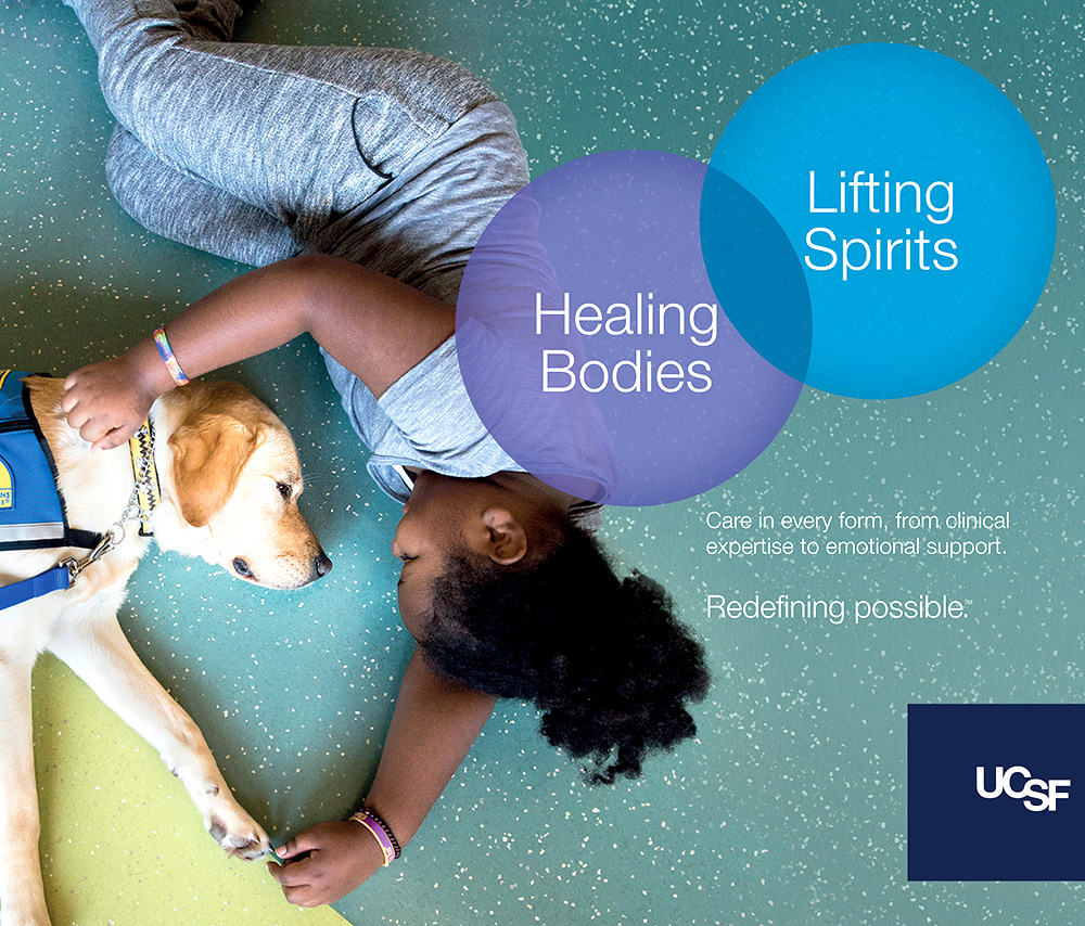 UCSF advertisement showing a girl petting a therapy dog. Text reads: Healing bodies, lifting spirits.