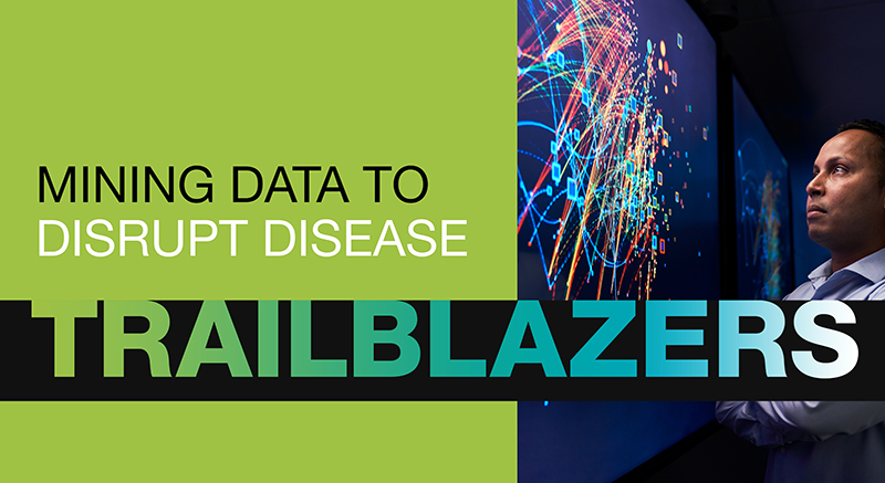 Researcher looking at data visualization next to the words Trailblazers: Mining data to disrupt disease