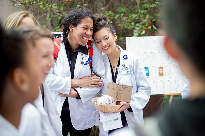 Students in white coats lean against one another in solidarity