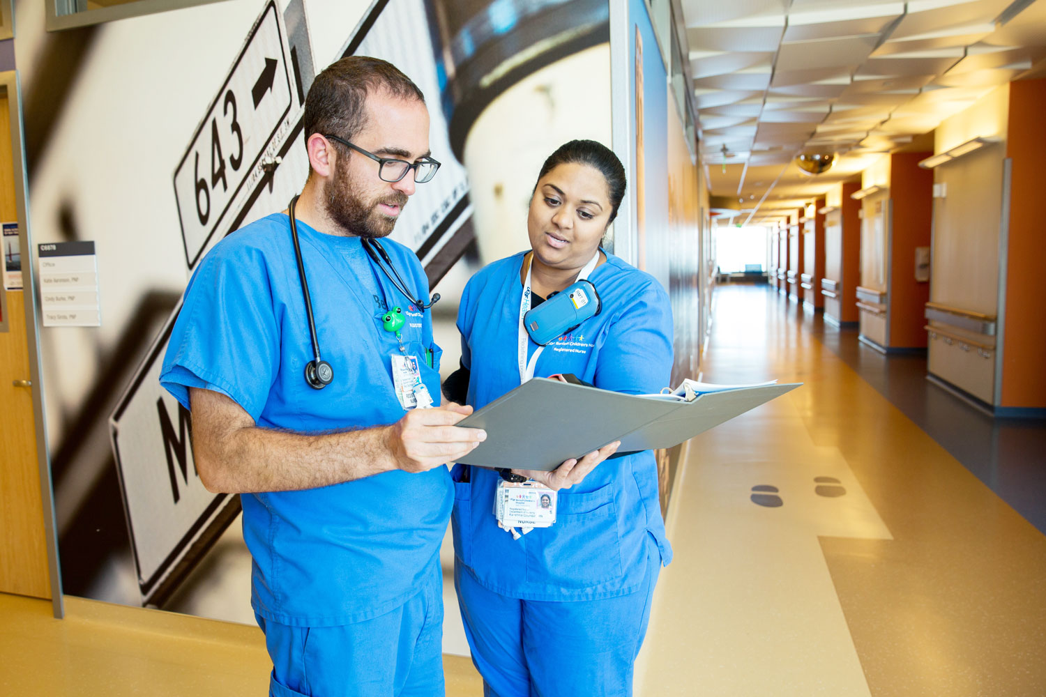 2 UCSF nurses talk in a hospital hallway