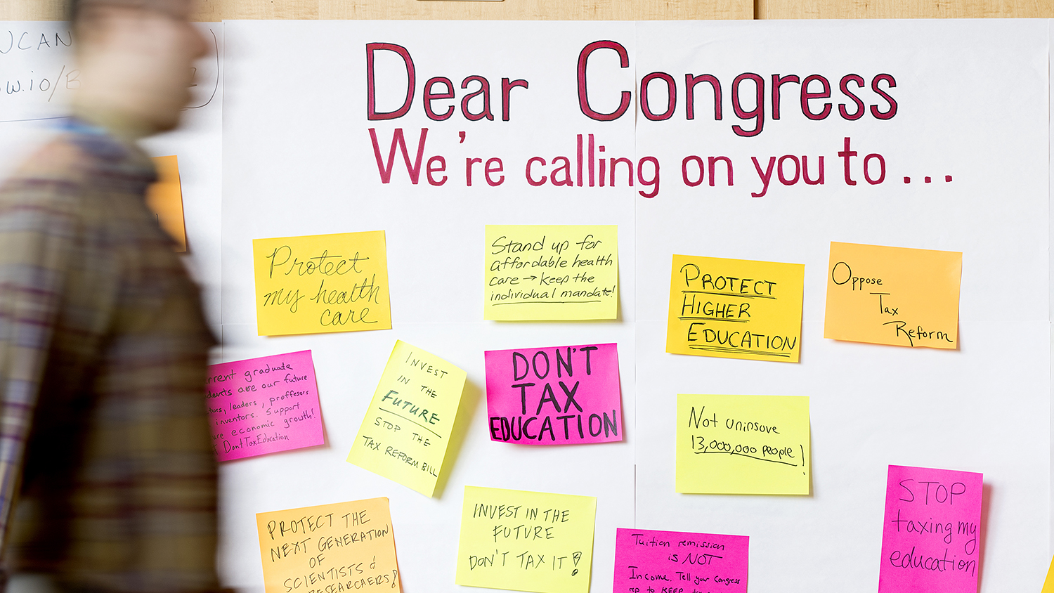 "a person walks past a whiteboard witht the words ""Dear Congress We're calling on you to..."""