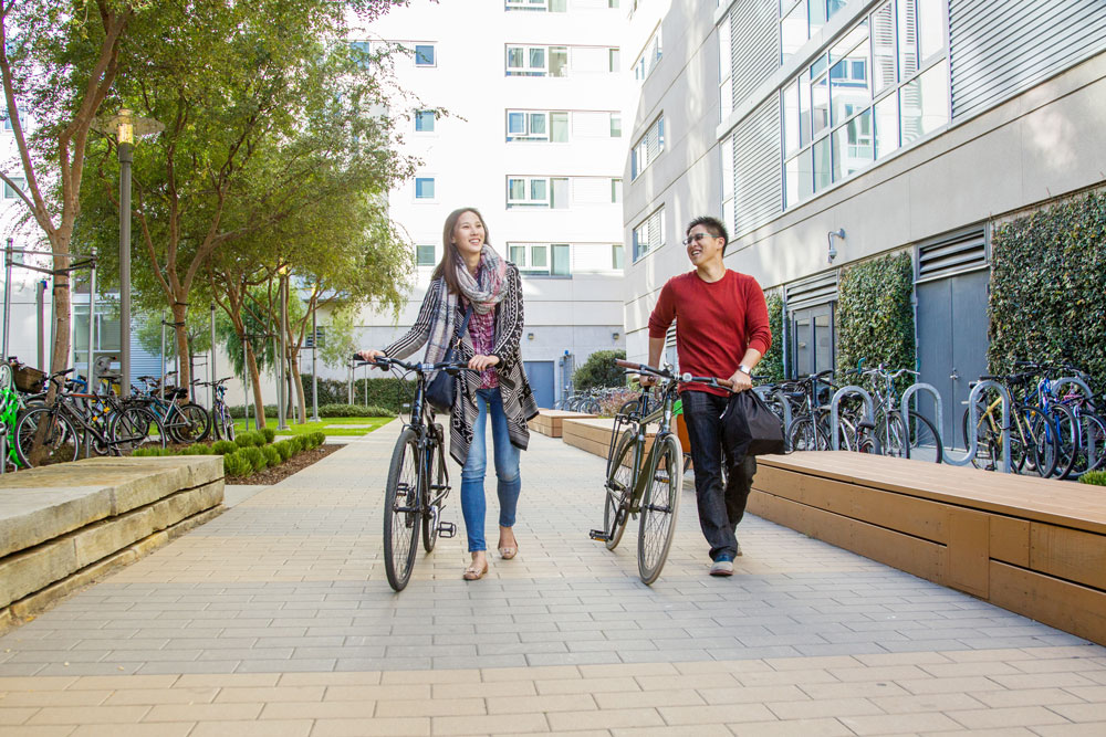 2 UCSF students walking their bikes through a housing complex