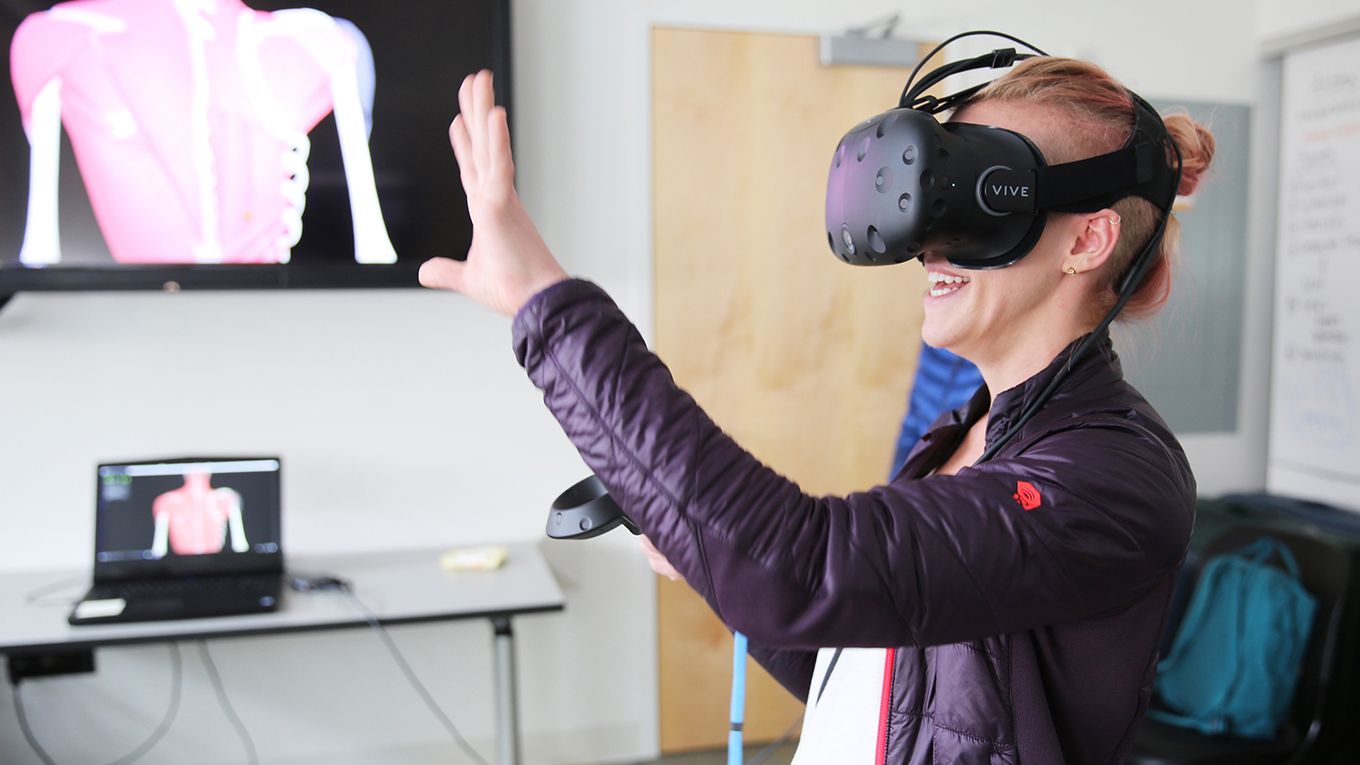 a student waves her hand while wearing a virtual reality headset