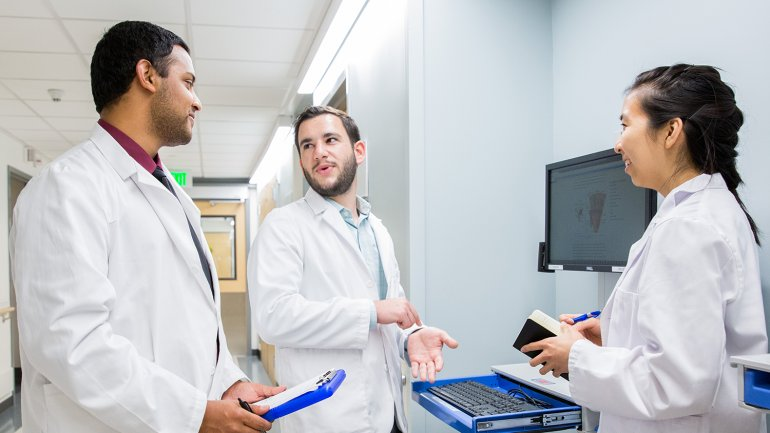 3 medical students talking in a hospital hallway