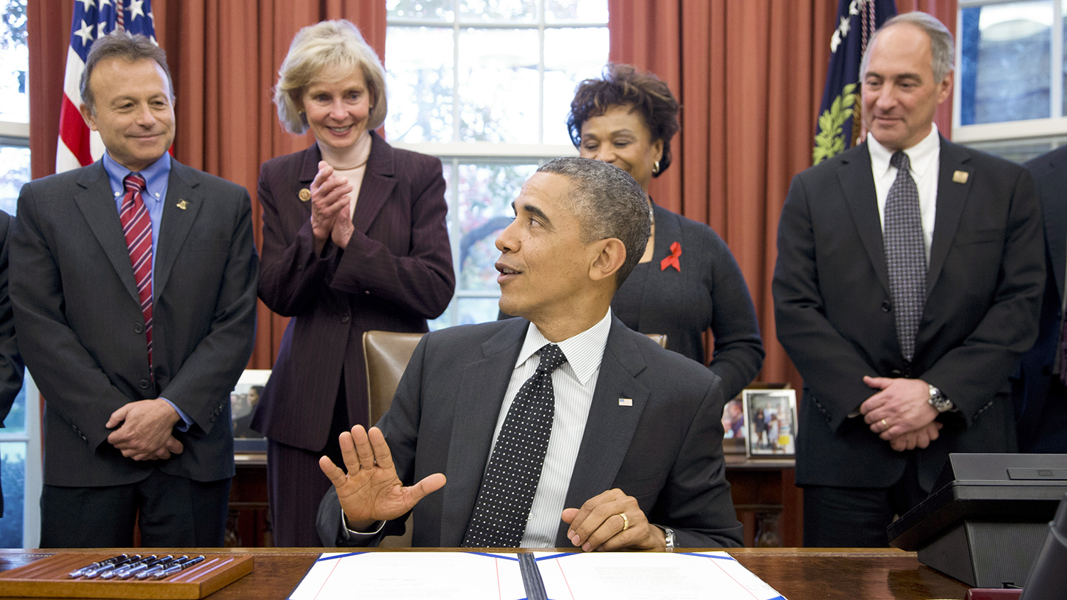 Barack Obama sits at a desk in the Oval Office; Peter Stock looks on