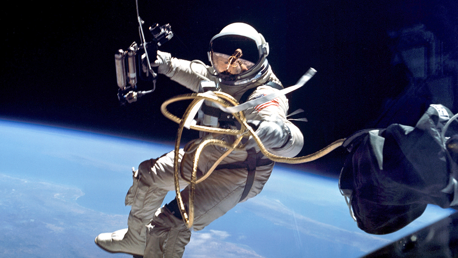 an astronaut on a spacewalk with Earth behind him