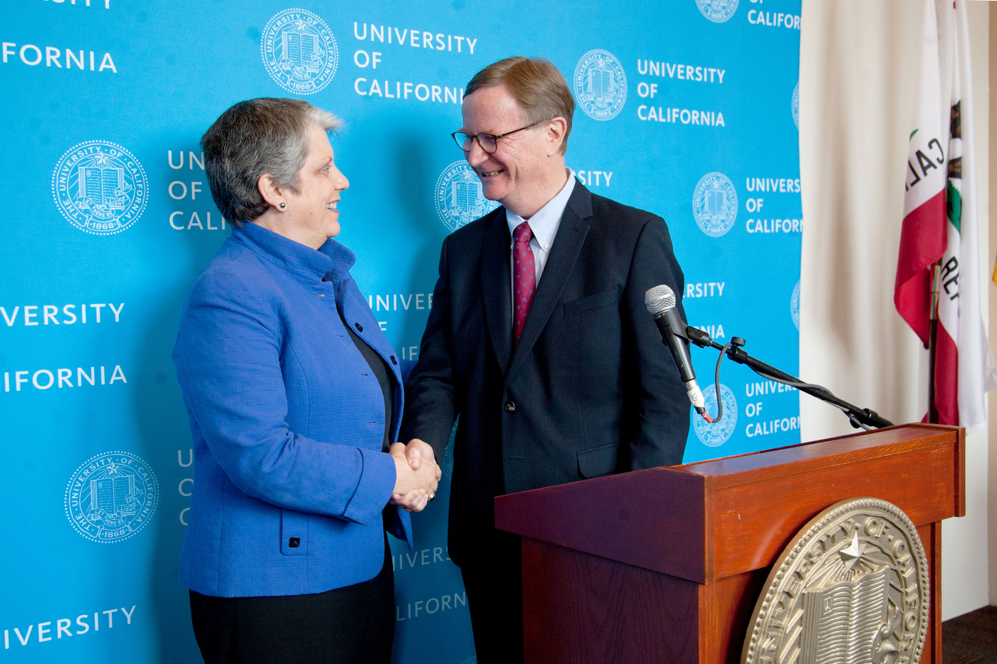 Janet Napolitano and Sam Hawgood shake hands at a press briefing after Hawgood was confirmed as UCSF's new chancellor