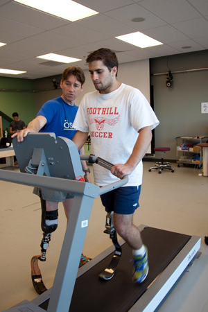 Trainer Jeff Turner looks on as Ranjit Steiner runs on treadmill at UCSF.