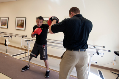Coach Tim Baldwin works on boxing techniques with Carlos Gonzalez.