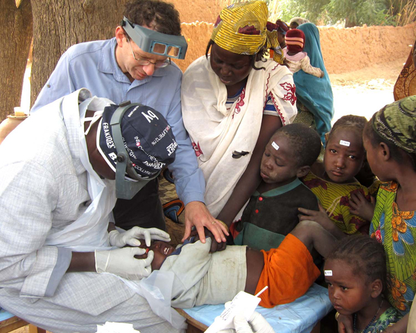 Bruce Gaynor and a colleague examine a young patient in an Ethiopian village.