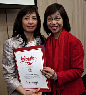Maxine Yee, right, presents a certificate of recognition.