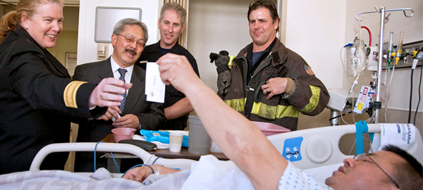 ne Hayes-White and Mayor Ed Lee visit with injured firefighter Stan Lee.