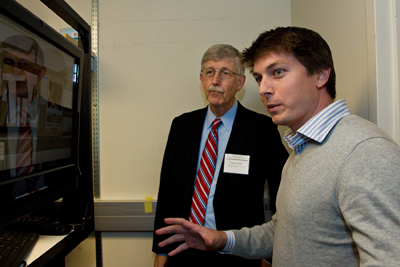Specialist Kyle Lapham demonstrates the ATLAS robot to Francis Collins