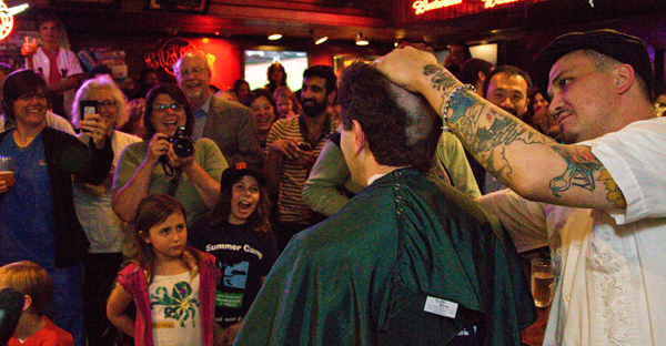 Crowd watches a H=head-shaving event to benefit childhood cancer research.