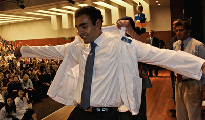 Jay S. Rajan receives help putting on his first white coat in an annual ceremony