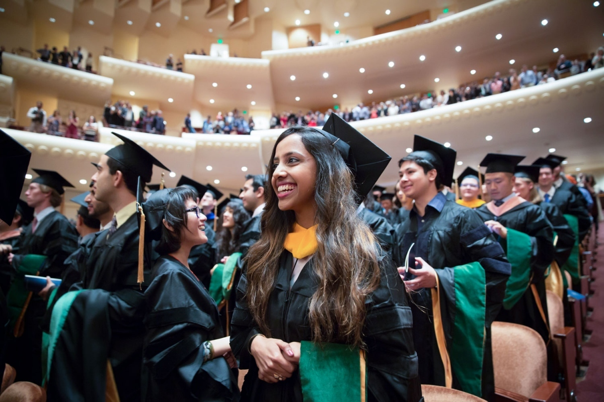 bd4866e1592 School of Medicine graduate Amlu Natesan stands with her classmates in the  Davies Symphony Hall auditorium. Photo by Elisabeth Fall