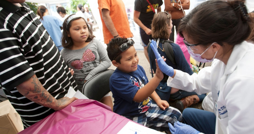 A dental student high-fives a child during a free dental screening at a Bayview street fair