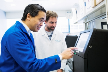 Charles Chiu and a colleague use a DNA sequencer