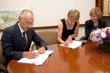 Michael Moritz and Harriet Heyman signing agreement