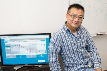 Xiao Hu, PhD, stands in front of his computer with information about patient-monitoring alarms