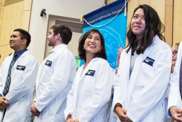 UCSF dental students line up on stage with white coats