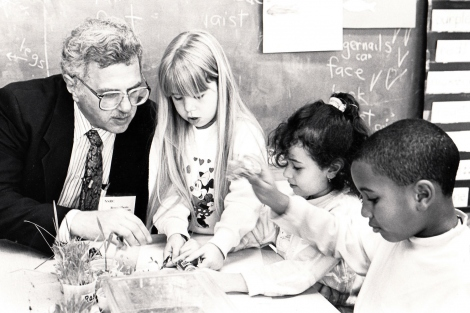 Bruce Alberts showing 3 kids something at a classroom table