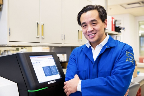 Charles Chiu stands in his lab next to a sequencing machine