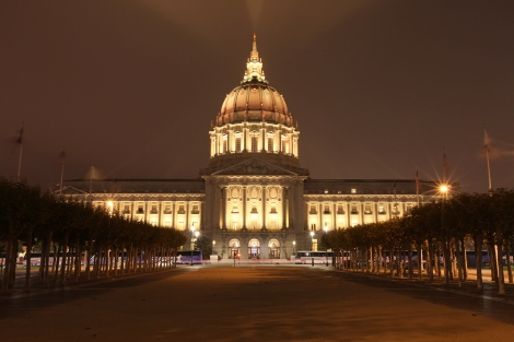 San Francisco City Hall is lit up with gold lights at night.