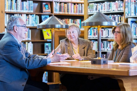 3 people discuss around a table at the library