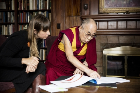 The Dalai Lama and Eve Ekman look at a booj about the Atlas of Emotions