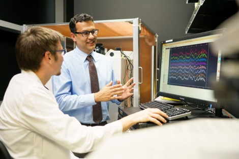 Neurologist Karunesh Ganguly and graduate student Stefan Lemke talk in front of a computer in the lab