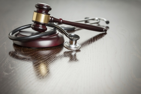 A gavel and stethoscope are shown in a stock photo