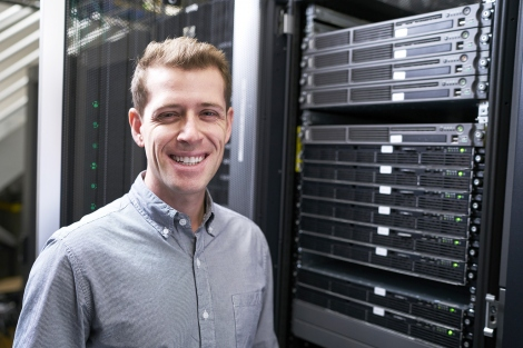 Michael Keiser stands in front of computer servers