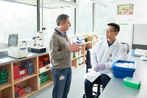 Ophir Klein talks with Nick Wang in a lab
