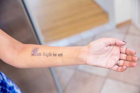 "Roopa Grewal shows her tattoo that reads ""How fragile we are"""