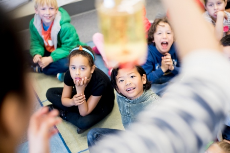 first graders look up and smile during a science experiment