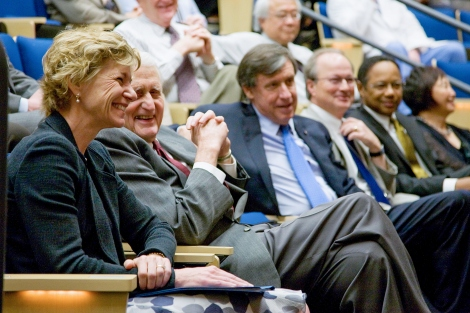 Susan Desmond-Hellmann and Holly Smith smile as they sit in a crowd in Cole Hall at UCSF's Parnassus campus