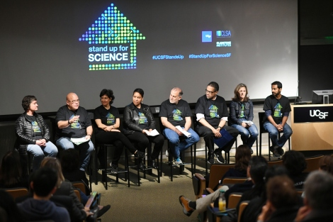 Eight members of the UCSF faculty sit on the stage during the Stand Up For Science teach-in in Genentech Hall