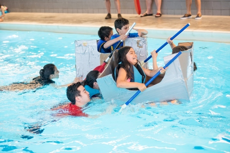 students race in handmade boats made from cardboard in a pool at UCSF's Mission Bay campus
