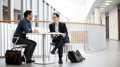 Edward Chang and Vikaas Sohal talk at a table in the Sandler Neurosciences Building