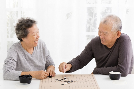 Asian elderly man and woman playing backgammon